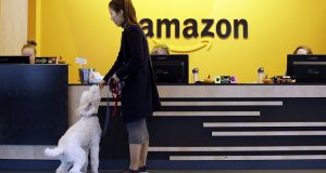 FILE - In this Wednesday, Oct. 11, 2017, file photo, an Amazon employee gives her dog a biscuit as the pair head into a company building, where dogs are welcome, in Seattle. Amazon says it received 238 proposals from cities and regions hoping to be the home of the company's second headquarters. The online retailer kicked off its hunt for a second headquarters in September, promising to bring 50,000 new jobs. It will announce a decision sometime in 2018. (AP Photo/Elaine Thompson, File)