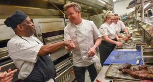 Chef Gordon Ramsay, center, shakes the hand of West Baltimore resident and sous chef, Andre Stith, after personally showing him some techniques in the kitchen at his new restaurant Gordon Ramsay Steak at Horseshoe Casino Baltimore during a press tour before its opening night party. (The Daily Record/Maximilian Franz