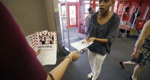 In this Friday, Oct. 13, 2017, photo, a potential job candidate takes a flyer from a human resources representative at a Target store in Dallas. The U.S. government issues the October jobs report, Friday, Nov. 3, 2017. (AP Photo/LM Otero)