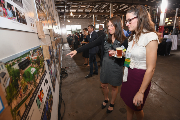 Lisa DeRose, left, a project scientist with Geo Technology Associates, and Brittany Sink, a designer with Morris Ritchie Associates, review the 35 award submission boards before casting their People's Choice vote during the ninth annual Urban Land Institute WaveMaker Awards. (Photo by Maximilian Franz)