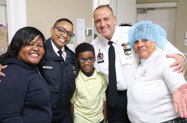 From left, Alicia Wilson, vice president of community affairs and legal adviser for Sagamore Development; Capt. Monique Brown, of the Baltimore police department's Southern District; Kaeden Edwards, a fourth-grader at Cecil Elementary; Maj. Steven Ward, of the Baltimore police department's Southern District; and a Baltimore Dream Center volunteer attended SB7 Coalition's Thanksgiving dinner. (Photo courtesy of Port Covington development team)