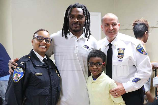 Baltimore Ravens corner back Brandon Carr takes a photo with Capt. Monique Brown, of the Baltimore police department's Southern District; Kaeden Edwards, a fourth-grader at Cecil Elementary; and Maj. Steven Ward, with the Baltimore police department's Southern District, during SB7 Coalition's Thanksgiving dinner. (Photo courtesy of Port Covington development team)