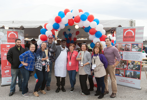 """The winners from the third annual Stars, Stripes and Chow Chili Cook-Off gather for a group photo, including teams from the Maryland Multi-Housing Association and Zeffert & Gold Catering, winners of """"Best Chili;"""" The Baltimore Station, which was named the """"People's Choice"""" winner; and Praxis Engineering, which won """"Best Booth"""" for its for its giant chuck wagon design and décor. (Photo courtesy of The Baltimore Station)"""