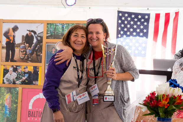 """From left, Iris Gold, an event manager with Zeffert & Gold Catering, gets a photo with Lori Crook, a staff member with the Maryland Multi-Housing Association, while Crook holds the """"Best Chili"""" trophy at the Stars, Stripes and Chow Chili Cook-Off. (Photo courtesy of The Baltimore Station)"""