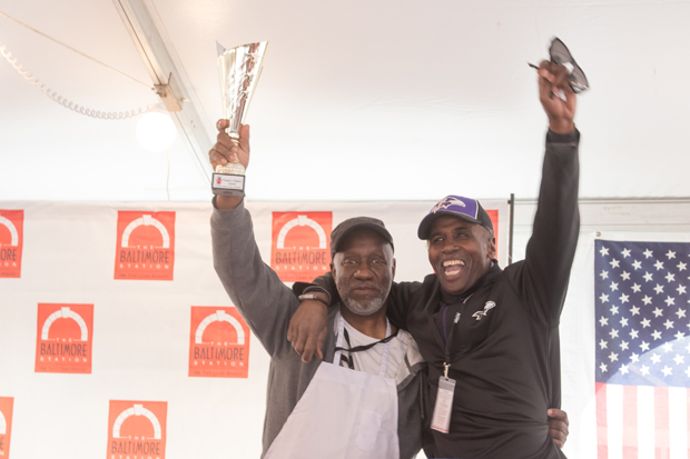 """Russell Jackson, left, the food services manager of The Baltimore Station, holds up the """"People's Choice"""" trophy as he takes a photo with Rodney Somerfield during the Stars, Stripes and Chow Chili Cook-Off. (Photo courtesy of The Baltimore Station)"""