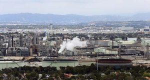 FILE - This May 25, 2017 aerial file photo shows the Standard Oil Refinery in El Segundo, Calif., with Los Angeles International Airport in the background and the El Porto neighborhood of Manhattan Beach, Calif., in the foreground. California Attorney General Xavier Becerra announced, Thursday, Dec. 7, 2017, that California is among fourteen states and the District of Columbia that are suing the Trump administration over what they say a failure to enforce smog standards. (AP Photo/Reed Saxon, File)