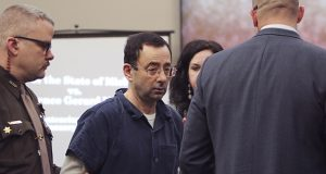 Larry Nassar arrives at court Tuesday, Jan. 16, 2018, for the first day of victim impact statements in Circuit Court Rosemarie Aquilina's courtroom in Lansing, Mich. Flanking Nassar are his attorneys Matt Newburg and Shannon Smith. Nassar pleaded guilty to molesting females with his hands at his Michigan State University office, his home and a Lansing-area gymnastics club. (Matthew Dae Smith/Lansing State Journal via AP)