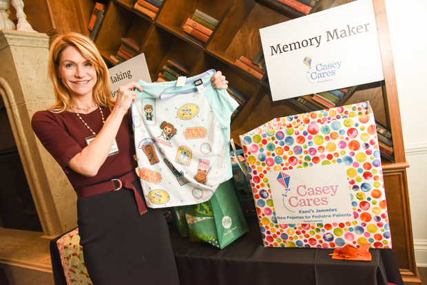 Jennifer Winslow, a director, portfolio manager with Harbor Investment Advisory LLC, holds up her donation of pajamas to the Casey Cares Foundation's Kami's Jammies program during the Path to Excellence networking event at Hotel Indigo. Attendees at the event donated 134 new pairs of pajamas to families served by Casey Cares, which was the nonprofit beneficiary of the event. (Photo by Maximilian Franz)