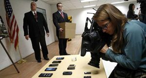A television news photographer films confiscated cell phones as officials prepare to return them to a box of evidence following a news conference at Jessup Correctional Institution in Jessup, Md., Thursday, Jan. 11, 2018. Maryland Gov. Larry Hogan and State Prosecutor Emmet Davitt announced indictments against two of the prison's corrections officers for allegedly attempting to smuggle in contraband for inmates that included drugs and cell phones. (AP Photo/Patrick Semansky)