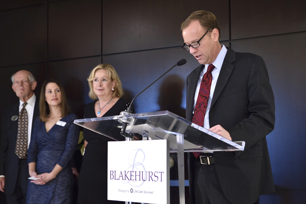 Pierce Linaweaver, right, president of the Blakehurst Residents' Association, delivers remarks to the crowd gathered for Blakehurst's ribbon-cutting opening in Towson. Joining Linaweaver on stage were Barb Clapp, the CEO of Clapp Communications; Allison Pendroy, senior vice president and director of for-profit communities with Life Care Services; and Curt Wagner, a project manager with LCS Development. (Photo by Tom O'Connor Photography)