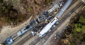 The wreckage of an Amtrak train, bottom, and a CSX freight train lie next to the tracks in Cayce, SC., on Sunday, Feb. 4, 2018. But whatever the precise legal language, plaintiffs' lawyers and former Amtrak officials say Amtrak generally bears the full cost of damages to its trains, passengers, employees and other crash victims — even in instances where crashes occurred as the result of a freight rail company's negligence or misconduct. (Jeff Blake/AP Photo)