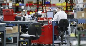 In this Oct. 24, 2017, photo, an employee wears his laboratory coat at his workstation at Lord Corporation, a manufacturer of industrial coatings, adhesives, bearings, and sensing equipment for range of commercial markets, including United States military contracts in Erie, Pa. Without white collar jobs, it becomes increasingly difficult for places to reinvent themselves at a moment when the global economy has prized brains over brawn. What can start as factory layoffs has snowballed into companies shifting their executive headquarters to cities with better airports, not just cheaper costs of doing business. (AP Photo/John Minchillo)