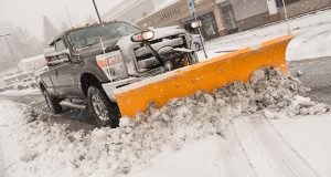 A plow clears a lot as snow falls Wednesday in Towson. (The Daily Record / Maximilian Franz)