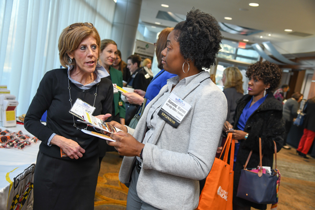 Leslie Wright, the director of programs for Baltimore with Citizenship Law Related Education Program,  speaks with Diamond Warren of Hotel Indigo Baltimore Downtown in the lobby of the BWI Hilton during the Women's Leadership Summit. (Photo by Maximilian Franz / The Daily Record)