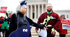 "Helenmary Ball, left, of Calvert County, Md., as ""Maryland District 5,"" points toward the separated area of Maryland District 3, being represented by Bobby Bartlett, right, as nonpartisan groups against gerrymandering protest in front of the Supreme Court, Wednesday, March 28, 2018, in Washington where the court will hear arguments on a gerrymandering case. The Supreme Court is taking up its second big partisan redistricting case of the term amid signs the justices could place limits on drawing maps for political gain. (AP Photo/Jacquelyn Martin)"
