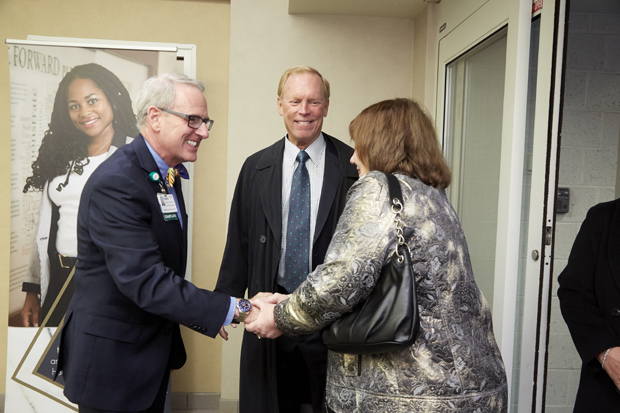 The Rev. J. Joseph Hart, M. Div, BCC, left, shakes hands with Roberta S. Kahlert, a member of the Kahlert Foundation board of directors while Greg W. Kahlert, president of The Kahlert Foundation looks on at the dedication ceremony of the William E. Kahlert Physicians Pavilion North building. (Photo by Tracey Brown, Papercamera Photography)