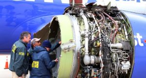 National Transportation Safety Board investigators examine damage to the engine of the Southwest Airlines plane that made an emergency landing at Philadelphia International Airport in Philadelphia on Tuesday. While Southwest has said it will work with victims' families, that may not preclude litigation down the road, although the precedent for liability based on emotional trauma or non-serious injuries is ambiguous. (NTSB via Associated Press)