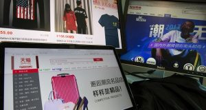 In this April 16, 2018, photo, computer screens display Alibaba's e-commerce website in Beijing, China. Executives tell AP their companies were punished by Alibaba after they refused to enter exclusive partnerships with the Chinese e-commerce giant. Traffic to their Tmall storefronts fell, hurting sales, as they fought for fair access to a $610 billion Chinese online marketplace. Alibaba says it offers perks for exclusivity but has never punished anyone. (AP Photo/Ng Han Guan)