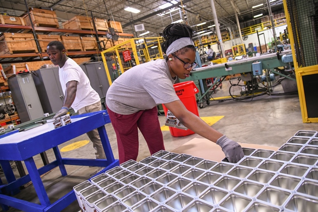 Line workers Iziah Lamons and China Smith take Swiss Miss hot chocolate tins off the assembly line at Independent Can Company. (Maximilian Franz/The Daily Record)