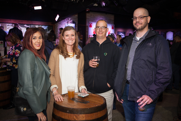 From left, Amanda Brooks, Homerun auction chair; Jennifer Rothenberger, Homerun event chair; Brad Fox, with Fortego; and Patrick Brooks, an associate with Booz Allen Hamilton, take in The Baltimore Station's 26th annual Homerun for Recovery fundraiser.