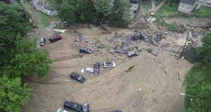 This image made from video provided by DroneBase shows vehicles swept by floodwater near the intersection of Ellicott Mills Drive and Main Street in Ellicott City, Md., Monday, May 28, 2018. Howard County Executive Allan Kittleman said Monday morning that his priorities are finding a missing man and assessing the condition of buildings that house shops, restaurants and families. (DroneBase via AP)