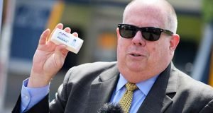 Gov. Larry Hogan holds a toll tag on Wednesday at the Bay Bridge toll plaza. Hogan announced the elimination of fees for the E-ZPass. (The Daily Record / Bryan P. Sears)