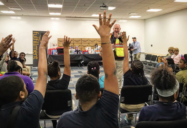 """Shan Byrne, director of operations for Amazon's Baltimore fulfillment center, at lectern, calls on a student who has a question during the Y in Central Maryland's """"Day at Amazon"""" tour. (Photo courtesy of the Y in Central Maryland)"""