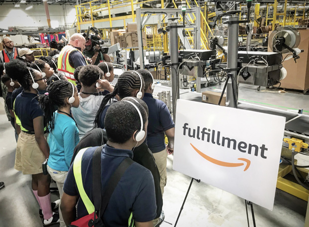 """Baltimore-area students wear headphones to see how robotics is used to sort packages during their """"Day at Amazon"""" tour. (Photo courtesy of the Y in Central Maryland)"""