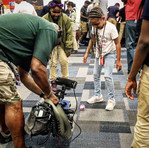 """A student participates in a demonstration of robotic technology during the Y in Central Maryland's """"Day at Amazon"""" tour. (Photo courtesy of the Y in Central Maryland)"""