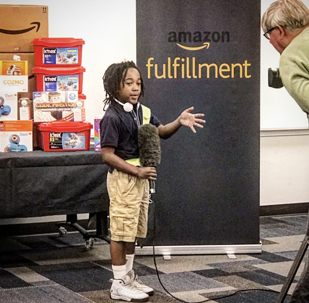 """A student tries out a microphone in a demonstration technology during the Y in Central Maryland's """"Day at Amazon"""" tour. (Photo courtesy of the Y in Central Maryland)"""