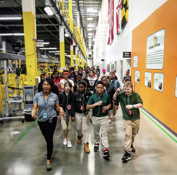 """Ashlee Partlow, a community engagement specialist at Amazon's Baltimore fulfillment center, leads students on a tour of the Amazon fulfillment center during the Y in Central Maryland's """"Day at Amazon"""" tour. (Photo courtesy of the Y in Central Maryland)"""