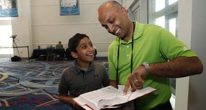 Dr. Balu Natarajan, right, from Hinsdale, Ill., poses for a photograph with his son Atman Balakrishnan, 12, as they look at Dr. Natarajan's winning word, at the Scripps National Spelling Bee, Tuesday, May 29, 2018, in Oxon Hill, Md. (AP Photo/Alex Brandon)