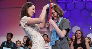 Nicole Tsygan, 12, from Parkton, Md., is presented with a medal to advance to the final round by Nicole Dittoe of Scripps National Spelling Bee during the Scripps National Spelling Bee in Oxon Hill, Md., Wednesday, May 30, 2018. (AP Photo/Carolyn Kaster)
