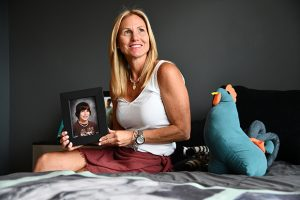 Tammy Lofink, founder and president of Rising Above Addiction, holds a photo of her son Robert in his bedroom where he died of an overdose in 2014. Photo by Maximilian Franz.