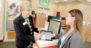 An employee at the PNC branch at 6227 N. Charles Street in Baltimore shows a customer PNC's Virtual Wallet program on a tablet. More bank customers are using technology for many of their banking needs, but branches are still available for key services.