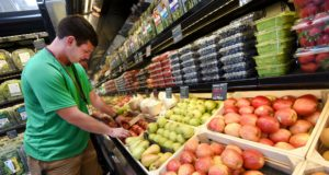 6-17-16 BALTIMORE, MD- Matt Hall, Produce Manager in Training, sorting through organic apples to place on the shelf in the produce section of Mom's Organic Market at the Rotunda complex in Hamden. (The Daily Record/Maximilian Franz)