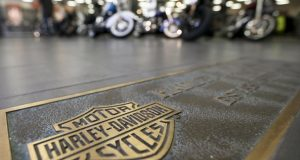 FILE - In this April 26, 2017, file photo, rows of motorcycles are behind a bronze plate with corporate information on the showroom floor at a Harley-Davidson dealership in Glenshaw, Pa. Harley-Davidson, facing rising costs from new tariffs, will begin shifting the production of motorcycles heading for Europe from the U.S. to factories overseas. (AP Photo/Keith Srakocic, File)