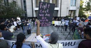 More than 100 protestors demonstrated outside the federal courthouse where a federal judge will hear arguments over the U.S. Justice Department's request to block three California laws that extend protections to people in the country illegally, Wednesday, June 20, 2018, in Sacramento, Calif. (AP Photo/Rich Pedroncelli)