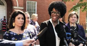 Valarie Ervin, center, speaks outside the Anne Arundel County Circuit courthouse Monday, accompanied by Marisol Johnson, left, and her attorney, Mariana Cordier. (The Daily Record / Bryan P. Sears)