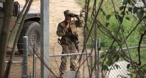 "FILE - In this April 10, 2018, file frame from video, a National Guardsman watches over Rio Grande River on the border in Roma, Texas. The governors of multiple East Coast states have announced that they will not deploy National Guard resources near the U.S.-Mexico border, a largely symbolic but politically significant rejection of the Trump administration's ""zero-tolerance"" immigration policy that has resulted in children being separated from their families. (AP Photo/John Mone, File)"