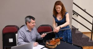 Violinist Ellen Pendleton Troyer has her instrument inspected in preparation for the Baltimore Symphony Orchestra's trip to the United Kingdom and Ireland next month. An instrument must be shown to have been legally imported or purchased in addition to being 'legally crafted' in the time it was made. (Courtesy Baltimore Symphony Orchestra)