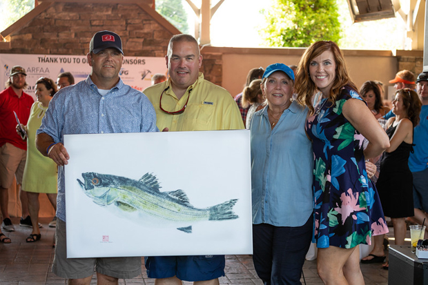 From left, Casey Cares Rockfish Tournament chair John Sovero, Captains Challenge winner Brett Sause, painter Nancy Cann Shimer and Casey Cares Executive Director and founder Casey Baynes pose with a painting created by Shimer during the event at The Inn at Chesapeake Bay Beach Club. (Photo by Yumi Okomoto Photography)