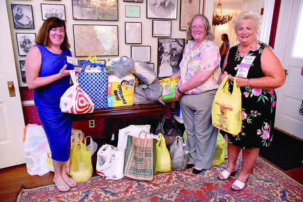 From left, Harford Family House staff members Kathy McGee and Mary Biggs and CEO Robin Tomechko stand with items donated to the organization during the networking event. Harford Family House was the the nonprofit beneficiary of the event. (Photo by Maximilian Franz / The Daily Record)