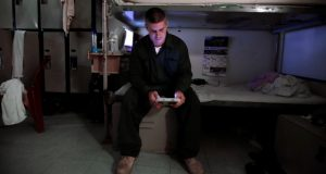 Inmate Anthony Plant reads from a tablet at his bunk at the Corrections Transitional Work Center, a low risk security section at the New Hampshire State Prison for Men, in Concord, N.H. Inmates across the country are getting access to technology via tablets in an effort to help their education, keep them connected to family and reduce noise and violence in prison. (Charles Krupa/AP photo)