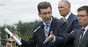 FILE - In this June 21, 2018, file photo, Washington state Attorney General Bob Ferguson, left, speaks as Washington Gov. Jay Inslee, center, and Solicitor General Noah Purcell look on at a news conference in SeaTac, Wash. Seven national fast-food chains have agreed to end policies that block workers from changing branches, limiting their wages and job opportunities, under the threat of legal action from the state of Washington. Ferguson announced the binding agreements with companies including Arby's, Jimmy John's and Cinnabon, Thursday, July 12, 2018. (AP Photo/Elaine Thompson, File)