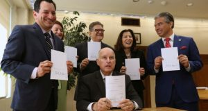 California Gov. Jerry Brown holds a copy of a bill to end bail he signed Tuesday, in Sacramento. The bill, co-authored by state Sen. Bob Hertzberg, D-Van Nuys, third from right, and Assemblyman Rob Bonta, D-Alameda, right, makes California the first state to eliminate bail for suspects awaiting trial. Also seen are Assembly Speaker Anthony Rendon, D-Lakewood, left, Senate President Pro Tem Toni Atkins, D-San Diego, second from left, and California Supreme Court Chief Justice Tani Cantil-Sakauye, second from right. (Rich Pedroncelli/AP photo)