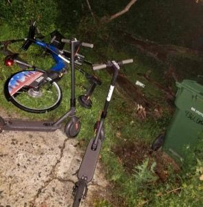 A dumped Baltimore Bike Share cycle dumped in a lot with two Bird electric scooters in West Baltimore. (Submitted Photo / Joel D. Murphy).