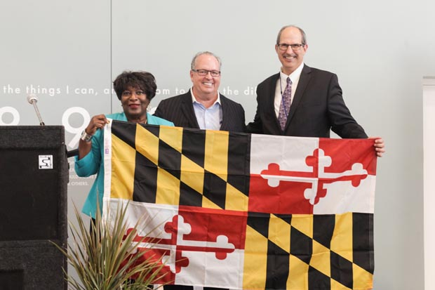 From left, District 28 Del. Edith Patterson, D-Charles County, Recovery Center of America founder and CEO Brian O'Neill and Maryland Center for Addiction Treatment CEO Adam Brickner display a Maryland flag that will fly at the new center in Waldorf. Patterson presented the flag and an official citation for the center's grand-opening event. (Photo by Bill Cassidy, Recovery Centers of America)