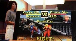 "A sign on display during Monday's meeting created by residents to illustrate their fight against the owner of Clipper Mill, uses imagery from the popular ""Street Fighter II"" video game series. Residents, led by Jessica Meyer at left, have fought the proposal for new building in the area.  (The Daily Record / Adam Bednar)"