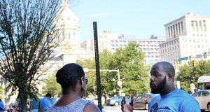 Tre Murphy, an organizer for Communities United, speaks to a passerby on Thursday about a new rental law in Baltimore. (The Daily Record / Adam Bednar)